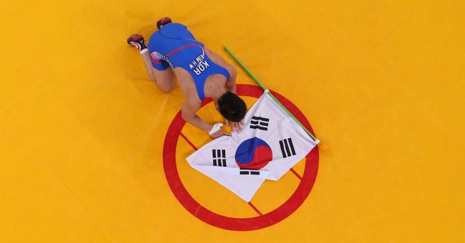 Sul-coreano Hyeonwoo Kim comemora vitória na luta greco-romana colocando bandeira de seu país no centro do tatame