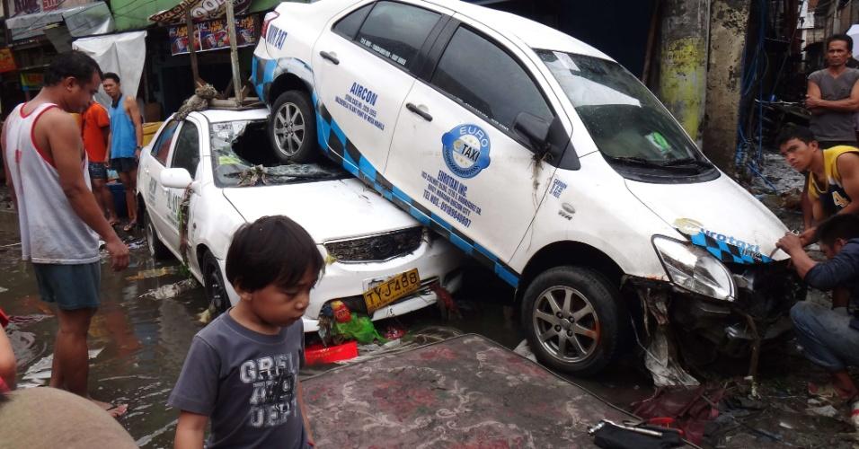 8.ago.2012 - Carros são arrastados pela água que inundou as ruas de Manila, nas Filipinas. Mais de 20 mil pessoas tiveram de ser evacuadas e levados a centros de assistência