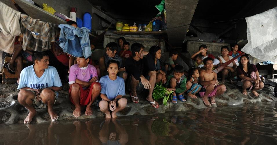 8.ago.2012 - Filipinos buscam abrigo embaixo de ponte em cidade ao norte de Manila, nas Filipinas, para se proteger das inundações em áreas próximas à capital filipina