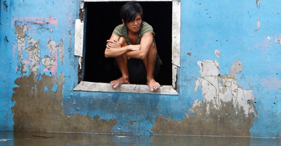 8.ago.2012 - Morador se protege das inundações na janela de casa, no distrito de Quezon, região metropolitana de Manila, nas Filipinas. Mais de 20 mil pessoas tiveram de ser evacuadas e levados a centros de assistência