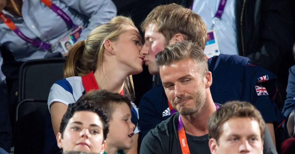 Ciclistas britânicos medalhistas de ouro, Laura Trott e Jason Kenny se beijam em arquibancada do vôlei de praia, atrás de David Beckham