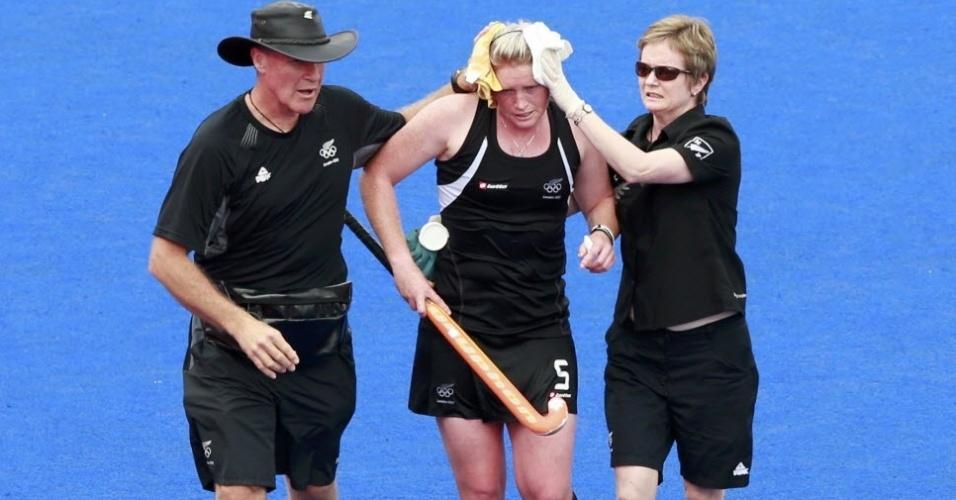 Katie Glynn, da Nova Zelândia, deixa o campo amparada pelos médicos após ser atingida na cabeça na semifinal feminina do hóquei na grama contra a Holanda