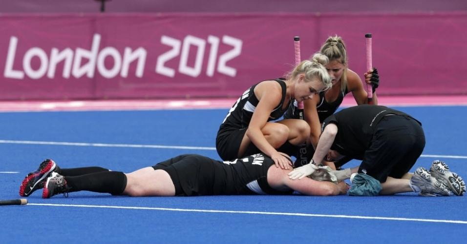 Katie Glynn, da Nova Zelândia, é atendida após ser atingida na cabeça na semifinal feminina do hóquei na grama contra a Holanda