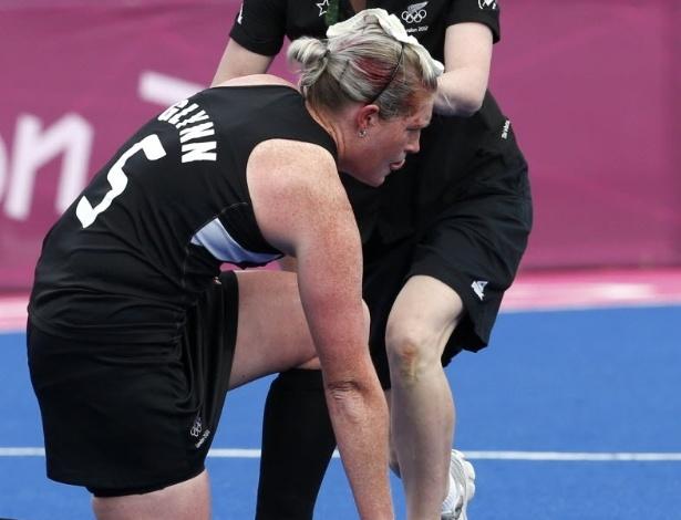 Katie Glynn, da Nova Zelândia, sangra após ser atingida na cabeça na semifinal feminina do hóquei na grama contra a Holanda e é atendida em campo