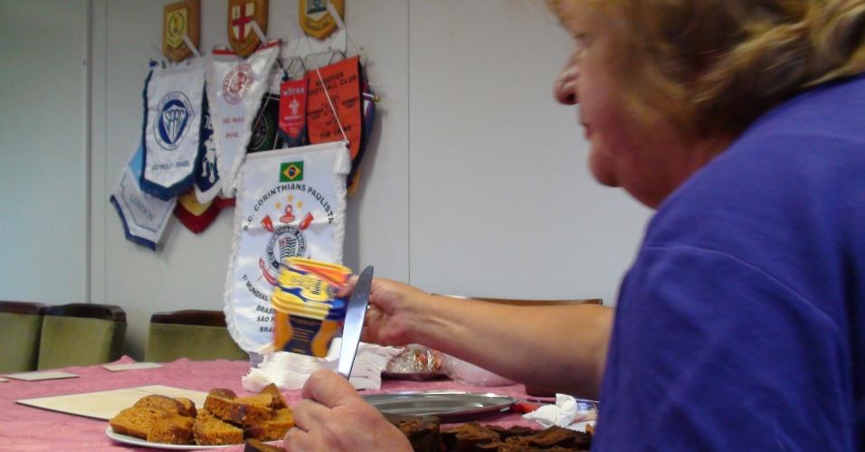 Na diretoria, senhora corta bolo e prepara café e chá para os dirigentes do time antes da partida contra a Scotland Yard