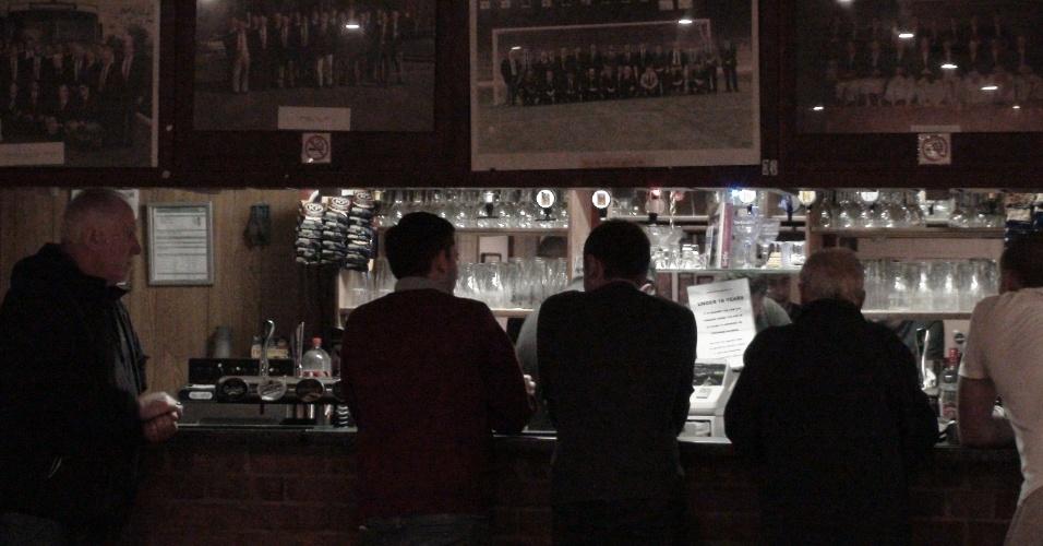 No intervalo do jogo, torcedores aproveitam o calor e a cerveja dentro do pub do clube londrino