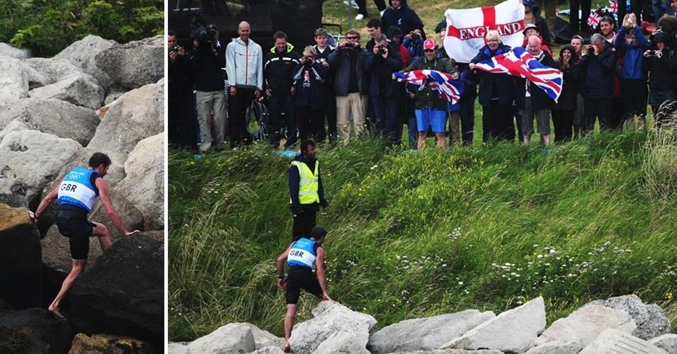 """O britânico Nick Dempsey conquistou a prata na classe RS:X e """"escalou"""" as pedras para comemorar com a torcida"""