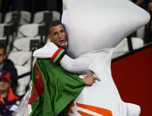 Taoufik Makhloufi, da Argélia, comemora com a mascote a vitória nos 1.500 m