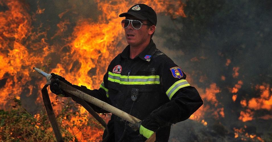 9.ago.2012 - Bombeiro tenta apagar incêndio na aldeia de Veliniatika, na Grécia