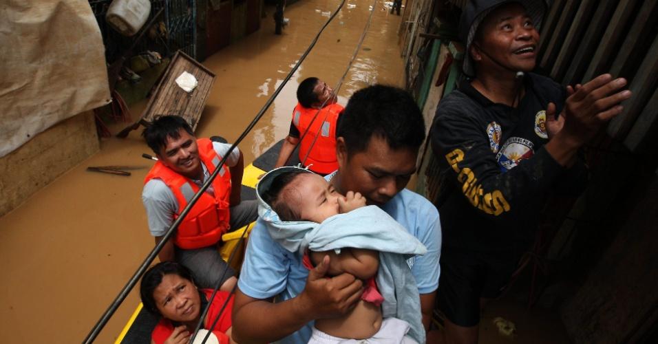 9.ago.2012 - Homem segura bebê no colo durante evacuação de moradores atingidos por alagamento na cidade de Marikina, nas Filipinas. Equipes de resgate aumentaram seus efetivos para ajudar cerca de dois milhões de pessoas afetadas pelas chuvas de monções em Manila, capital filipina, e nas cidades vizinhas. Ao menos 24 mortes foram provocadas pelo mau tempo