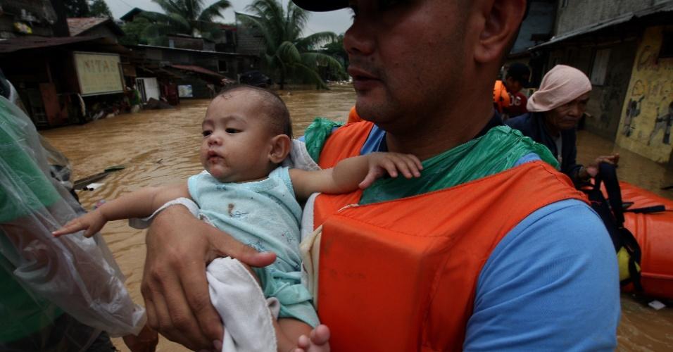9.ago.2012 - Policial filipino segura bebê no colo durante evacuação de moradores atingidos por alagamento na cidade de Marikina, nas Filipinas. Equipes de resgate aumentaram seus efetivos para ajudar cerca de dois milhões de pessoas afetadas pelas chuvas de monções em Manila, capital filipina, e nas cidades vizinhas. Ao menos 24 mortes foram provocadas pelo mau tempo Rolex Dela Pena/EFE