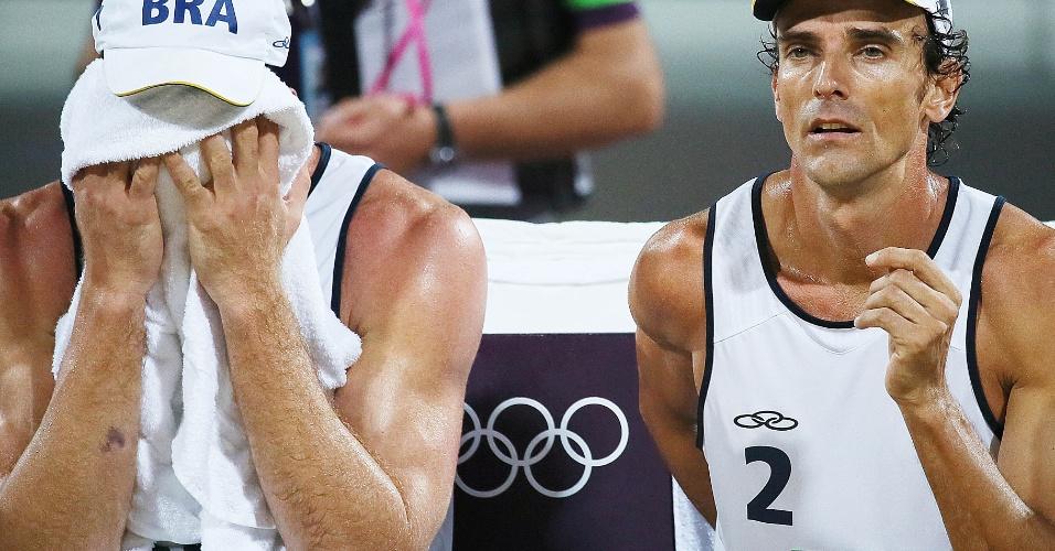 Alison esconde o rosto, e Emanuel fica com cara fechada após derrota da dupla brasileira na final olímpica