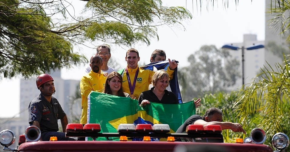 Arthur Zanetti exibe a medalha de ouro olímpica durante desfile em carro aberto dos Bombeiros