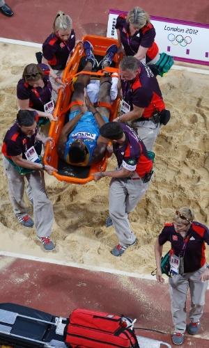 09.ago.2012 - Leevan Sands, de Bahamas, é retirado de maca após se machucar em uma tentativa na final do salto triplo dos Jogos de Londres