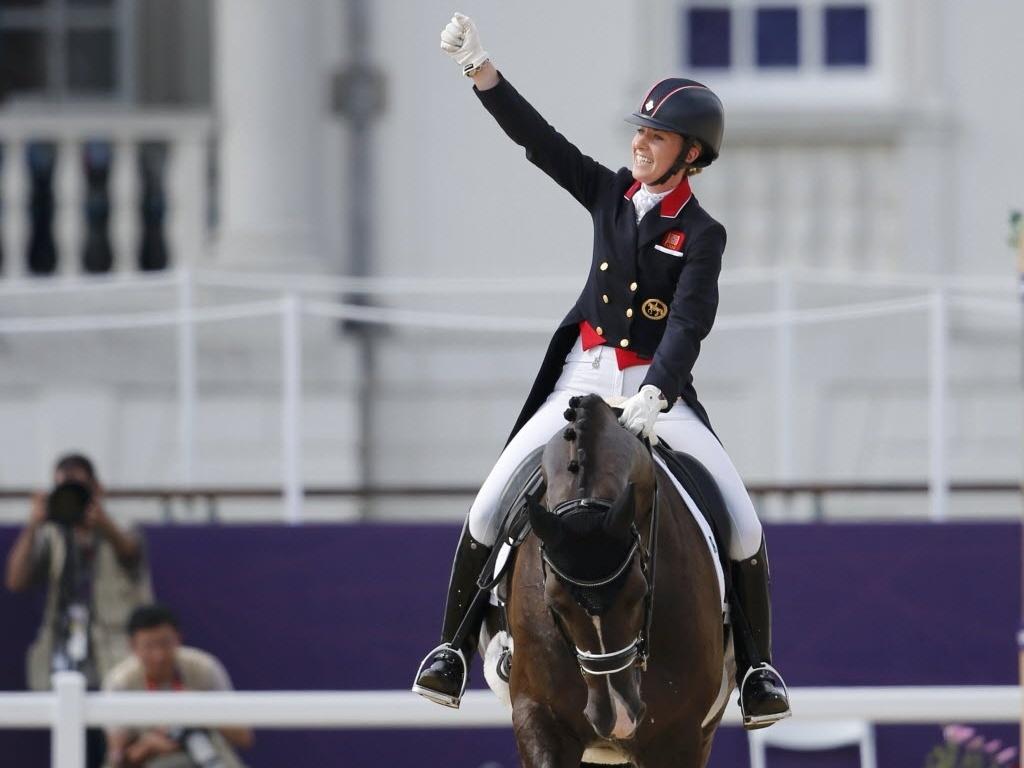 Montada no cavalo Valegro, a britânica Charlotte Dujardin comemora a medalha de ouro conquistada no adestramento individual (09/08/2012)