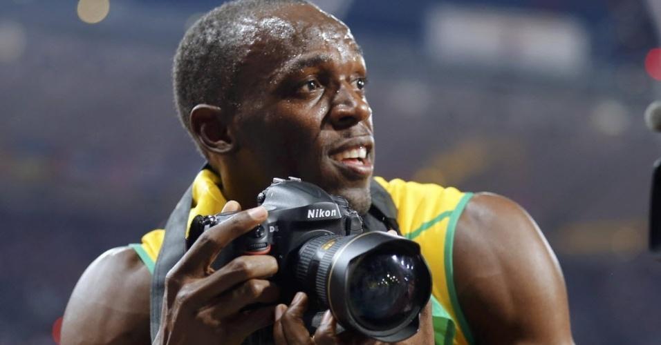 """Usain Bolt """"rouba"""" máquina de fotógrafos na comemoração do bicampeonato olímpico dos 200 m"""