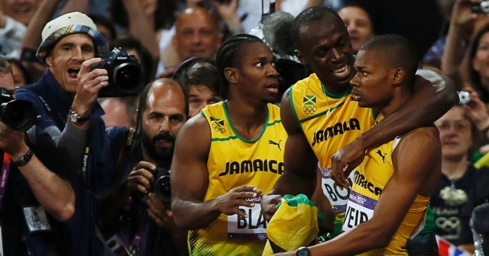 Warren Weir, medalhista de bronze, é abraçado por Usain Bolt, que levou o ouro, com Yohan Blake, medalhista de prata, ao lado
