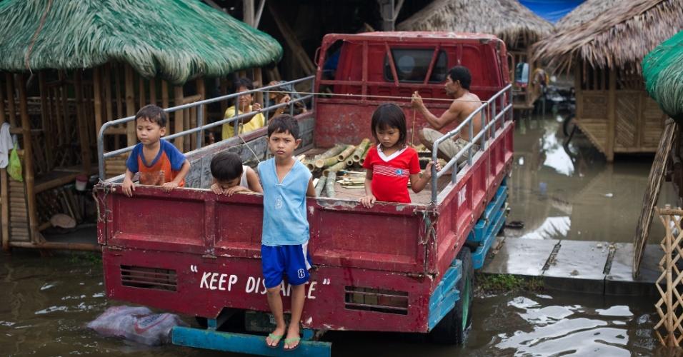 10.ago.2012 - Crianças sobem em carroceria de caminhão para se proteger das inundações que afetam as ruas de Apalit, nos arredores de Manila (Filipinas), nesta sexta-feira (10)