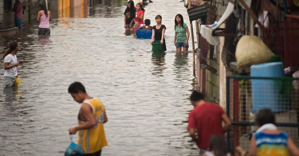 10.ago.2012 - Filipinos percorrem ruas inundadas no município de Apalit, nos arredores da capital filipina, Manila