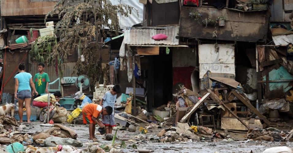 10.ago.2012 - Filipinos retiram água e barro de área inundada em San Mateo, província de Rizal, a oeste de Manila