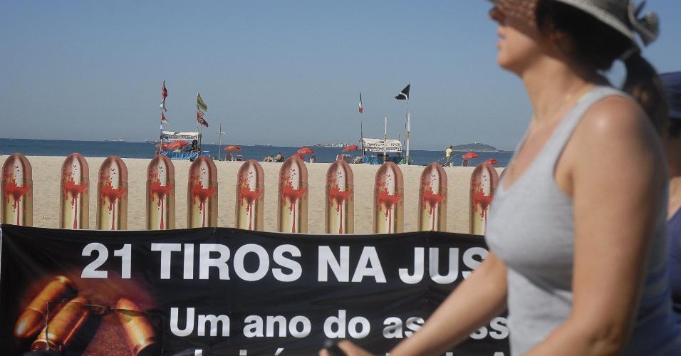 10.ago.2012 - Pedestre caminha em frente às 21 fotos de balas de revolver que ocupam as areias da praia de Copacabana, no Rio, na sexta-feira (10), nas vésperas do dia que completa um ano do assassinato da juíza Patricia Acioli. O protesto foi organizado pela ONG Rio de Paz