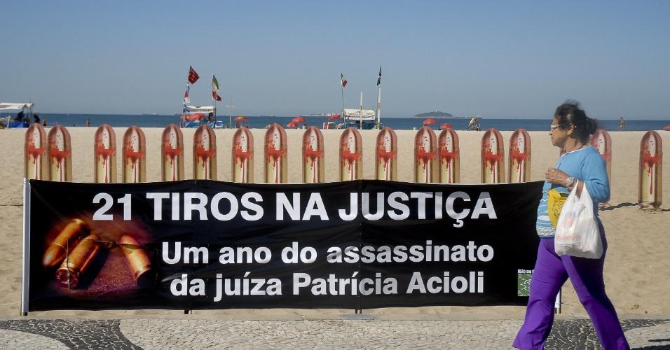 10.ago.2012 - Pedestre obsereva fotos de balas de revolver que ocupam as areias da praia de Copacabana, no Rio, na sexta-feira (10), nas vésperas do dia que completa um ano do assassinato da juíza Patricia Acioli. O protesto foi organizado pela ONG Rio de Paz