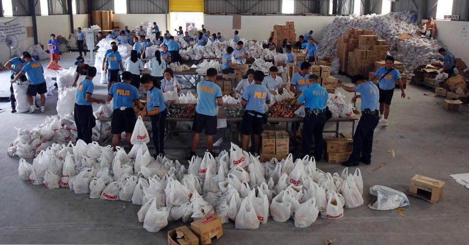 10.ago.2012 - Policiais filipinos ajudam freiras católicas a embalar alimentos e outros itens de necessidade básica nesta sexta-feira (10), no Departamento de Assistência e Desenvolvimento Social em Pasay City, nas Filipinas