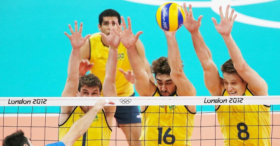 Bloqueio triplo do Brasil, com Bruninho (e.), Lucão e Murilo (d.), impede ataque do italiano Savani