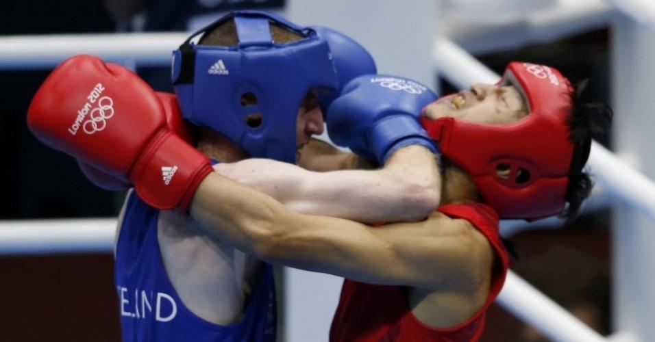Chinês Zou Shiming tenta se desvencilhar do ataque do irlandês Paddy Barnes na semifinal da categoria até 49 kg