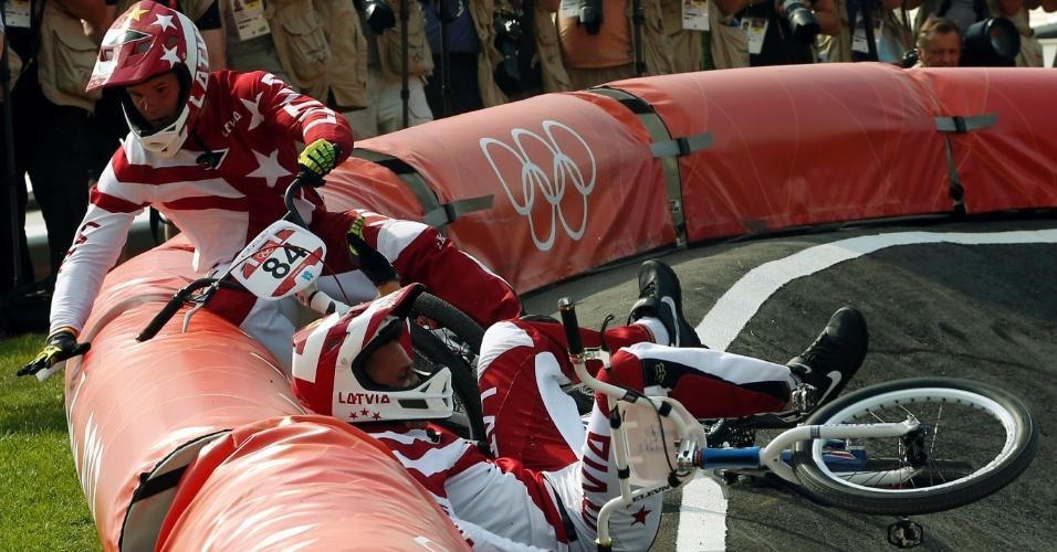 Compatriotas, Rihards Veide (e.) e Edzus Treimanis, da Letônia, trombam durante semifinal do BMX masculino