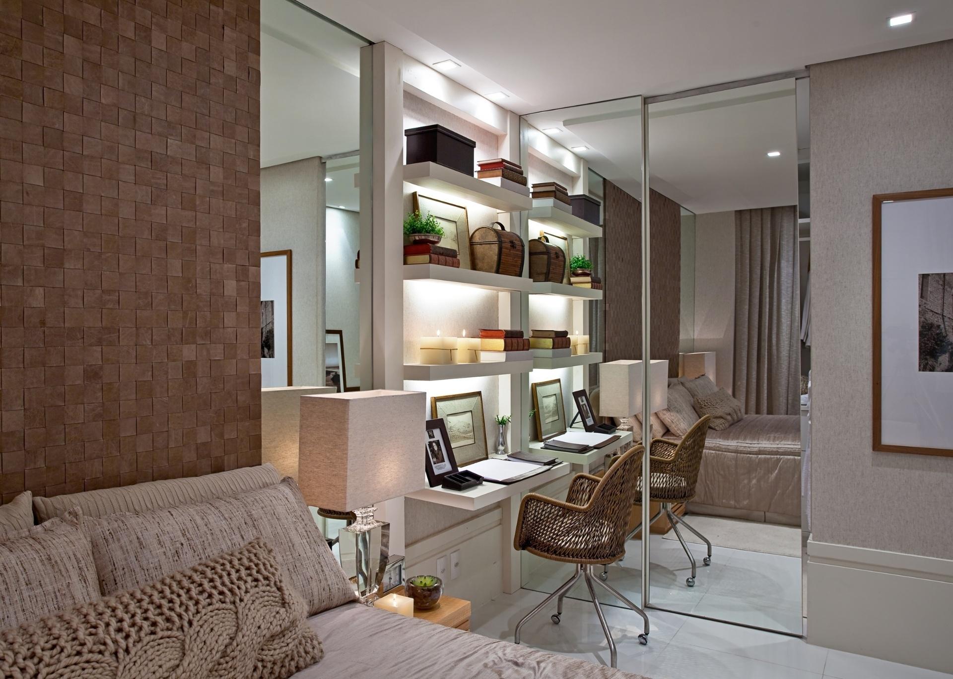 Deste ponto de vista, é notável que a área de trabalho criada por Maithia Guedes conecta-se estruturalmente ao closet. As superfícies espelhadas ampliam o ambiente e distribuem a iluminação natural do ambiente