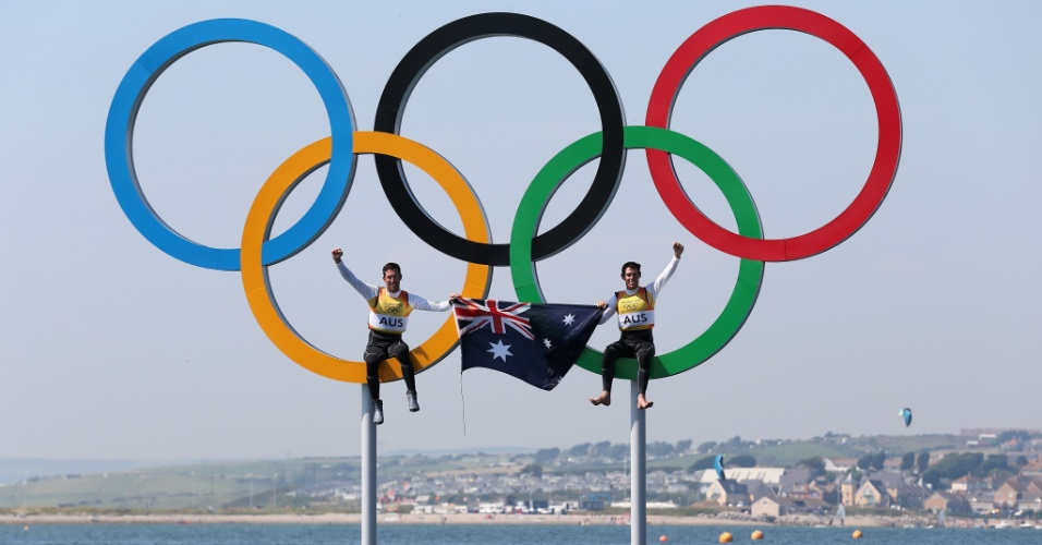"Os australianos Mathew Belcher (dir) and Malcolm Page ""escalaram"" os aros olímpicos para comemorar a medalha de ouro na classe 470 da vela masculina"