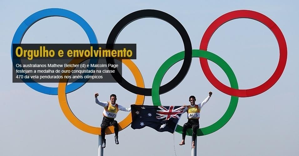 Os australianos Mathew Belcher (d) e Malcolm Page festejam a medalha de ouro conquistada na classe 470 da vela pendurados nos anéis olímpicos