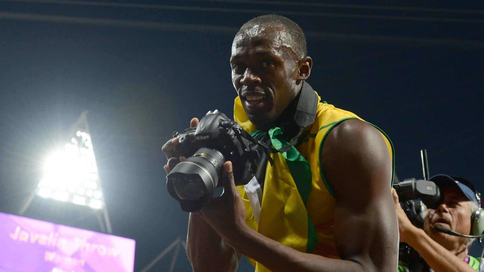 Usain Bolt pega câmera de fotógrafo na comemoração da vitória nos 200m rasos