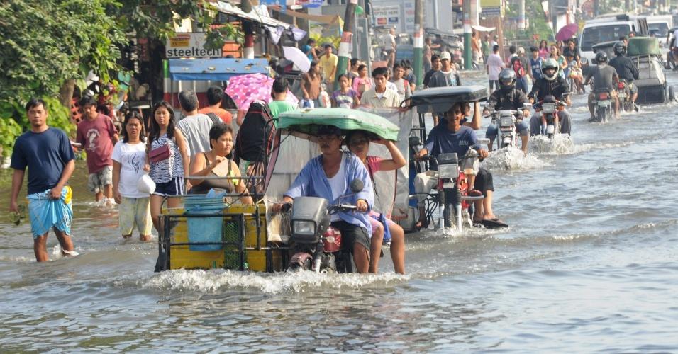 11.ago.2012 - Moradores se locomovem em trecho alagado da cidade de Calumpit, ao norte de Manila (Filipinas)