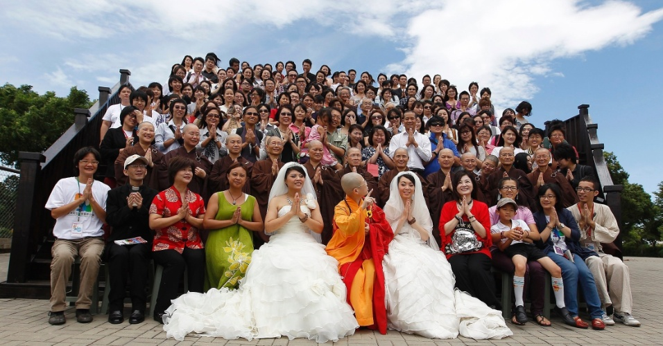 11.ago.2012 - You Ya-ting (direita) e Huang Mei-yu posam para foto com parentes e amigos depois da cerimônia simbólica de casamento realizada neste sábado (11) em um templo budista na cidade de Taoyuan, em Taiwan. Elas se casaram depois de sete anos de namoro. Foi o primeiro casamento gay budista na ilha
