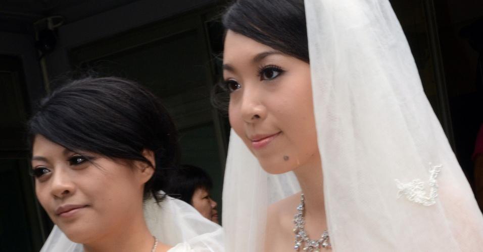 11.ago.2012 - You Ya-ting (direita) e sua companheira Huang Mei-yu se casaram em uma cerimônia simbólica neste sábado (11) em um templo budista na cidade de Taoyuan, em Taiwan. Foi o primeiro casamento gay budista realizado na ilha, que ainda não reconhece oficialmente a união de pessoas do mesmo sexo