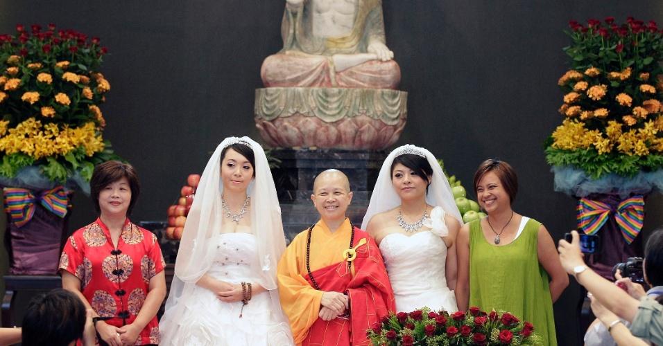 11.ago.2012 - You Ya-ting (esquerda) e Huang Mei-yu posam para foto com amigos e parentes depois da cerimônia simbólica de casamento celebrada neste sábado (11) em um templo budista em Taoyuan, em Taiwan. Foi o primeiro casamento gay budista na ilha. Elas esperam que a cerimônia sirva de exemplo para que a cidade se torne a primeira da Ásia a legalizar a união de pessoas do mesmo sexo