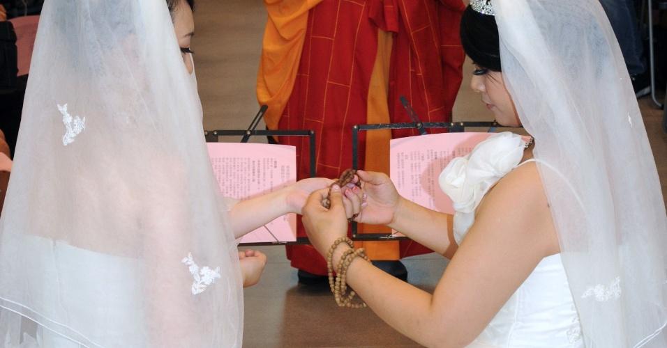 11.ago.2012 - You Ya-ting (esquerda) e Huang Mei-yu trocam terços budistas durante cerimônia de casamento realizada neste sábado (11) na cidade de Taoyuan, em Taiwan. Foi o primeiro casamento gay budista da ilha