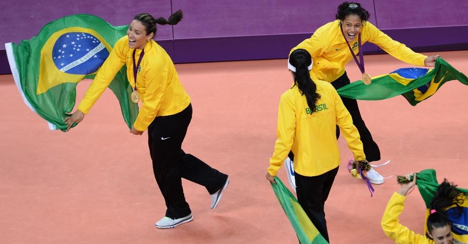Após receberem as medalhas de ouro, meninas comemoram com a bandeira do Brasil