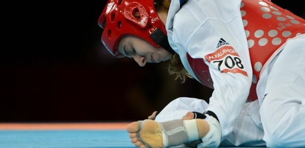 Natália Falavigna segura a perna durante o primeiro round da derrota para coreana na estreia do taekwondo