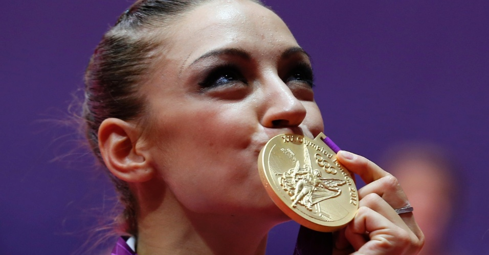 Russa Evgeniya Kanaeva beija a medalha de ouro conquistada na final individual de ginástica rítmica; ela se sagrou bicampeã olímpica