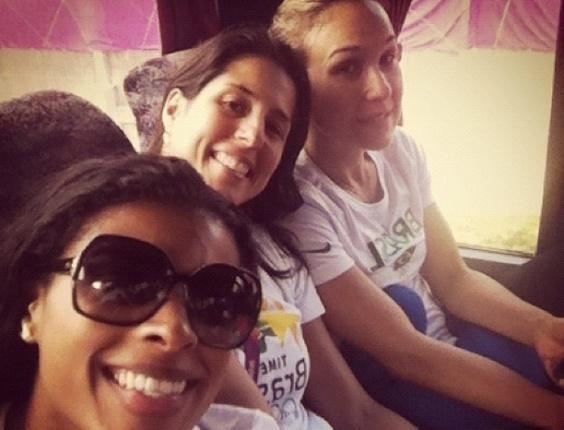 Fernanda Garay tira foto dentro de ônibus, ao lado de membro da comissão técnica e de Fernandinha