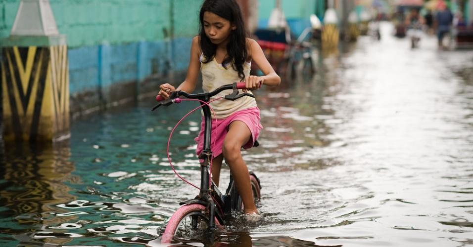 13.ago.2012 - Menina atravessa de bicicleta uma rua alagada em Valenzuela, bairro do subúrbio de Manila, capital das Filipinas, nesta segunda-feira (13). As autoridades filipinas emitiram sinal de alerta para intensificação das tempestades