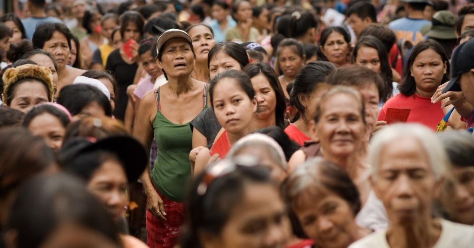 13.ago.2012 - Multidão afetada por inundações faz fila para receberem alimentos distribuídos pela Cruz Vermelha em Valenzuela, bairro do subúrbio de Manila, capital das Filipinas, nesta segunda-feira (13)
