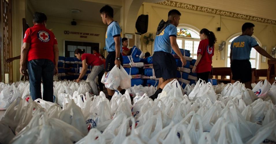 13.ago.2012 - Policiais Filipinos e voluntários da Cruz Vermelha organizam distribuição de alimentos para vítimas de inundações em uma igreja de Valenzuela, bairro do subúrbio de Manila, capital das Filipinas