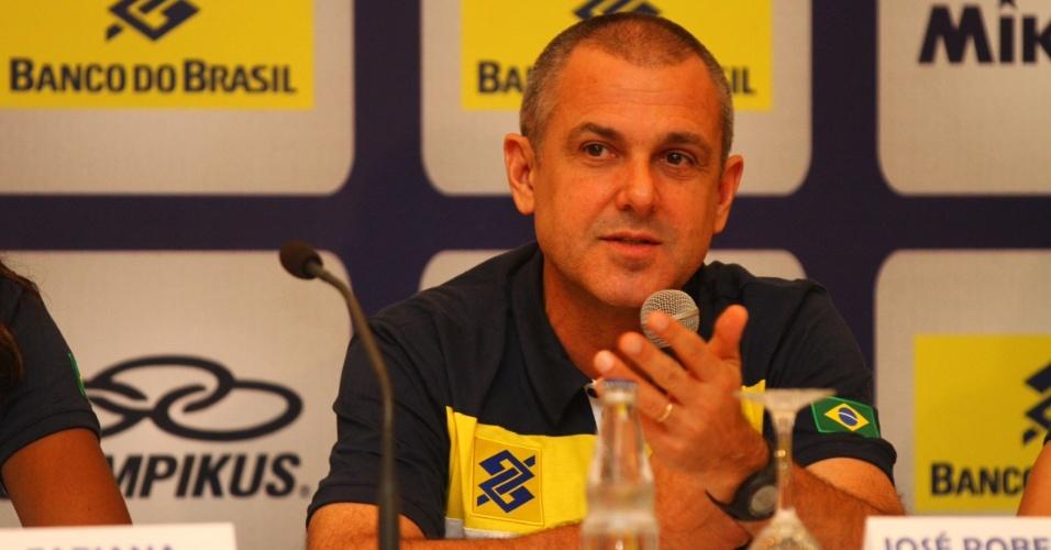 José Roberto Guimarães concede entrevista após desembarcar no Brasil. Técnico do vôlei feminino raspou a cabeça para pagar promessa após se tornar o primeiro tricampeão olímpico do Brasil