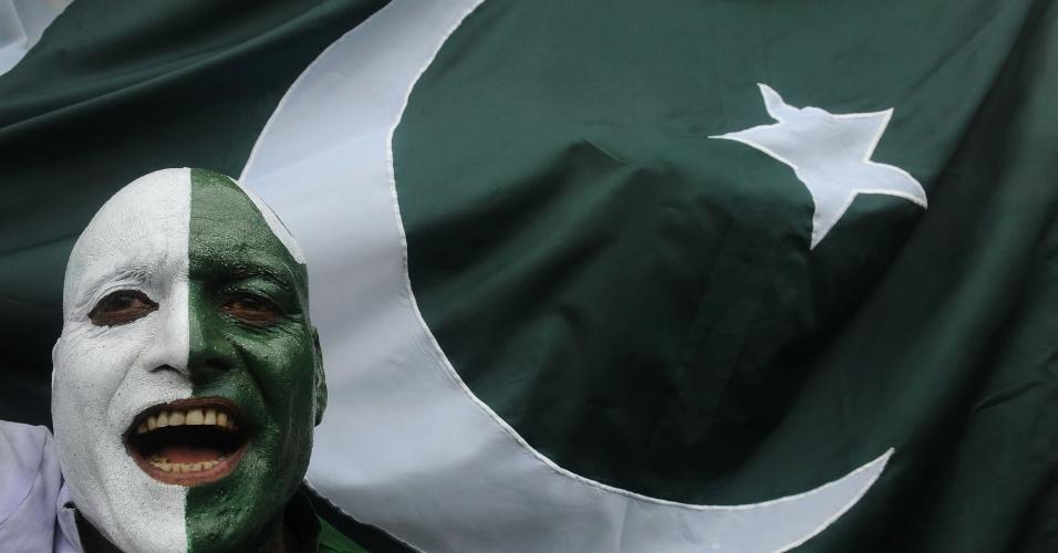 14.ago.2012 - Paquistanês com o rosto pintado com as cores do país celebra com a bandeira do Paquistão os 65 anos da independência do país, em Wagah, na fronteira entre Paquistão e Índia