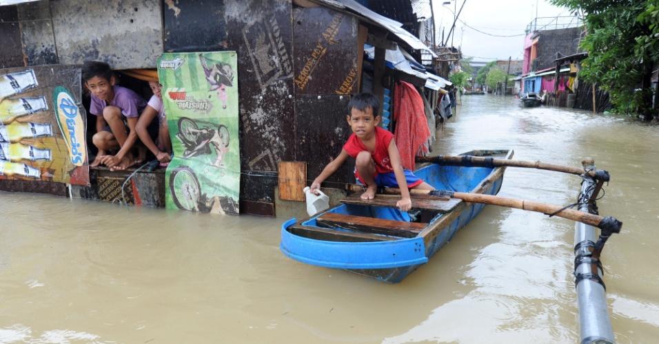 15.ago.2012 - Crianças buscam abrigo em barco e casa flutuante em Manila, capital das Filipinas, nesta quarta-feira (15). Quatro pessoas morreram depois que a tempestade tropical Kai-tak atingiu o país