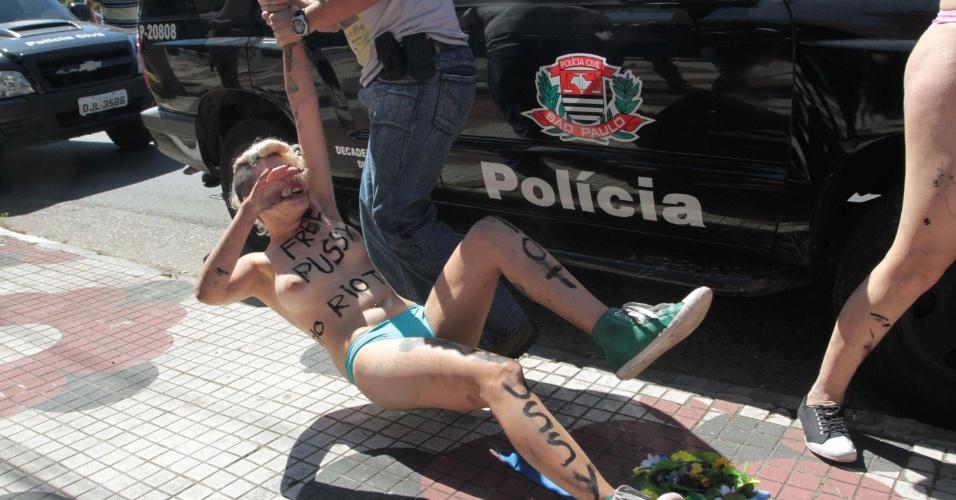 15.ago.2012 - Integrante do grupo Femen é arrastada por policial ao ser detida durante um protesto em prol da liberdade de três integrantes da banda russa Pussy Riot, em frente ao consulado da Rússia, em São Paulo. As três russas foram detidas devido a um protesto realizado em uma igreja, quando cantaram uma música intitulada